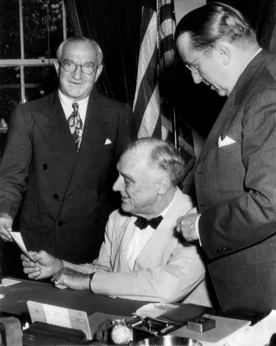 Nicholas M. Schenk (far left) hands check to FDR.