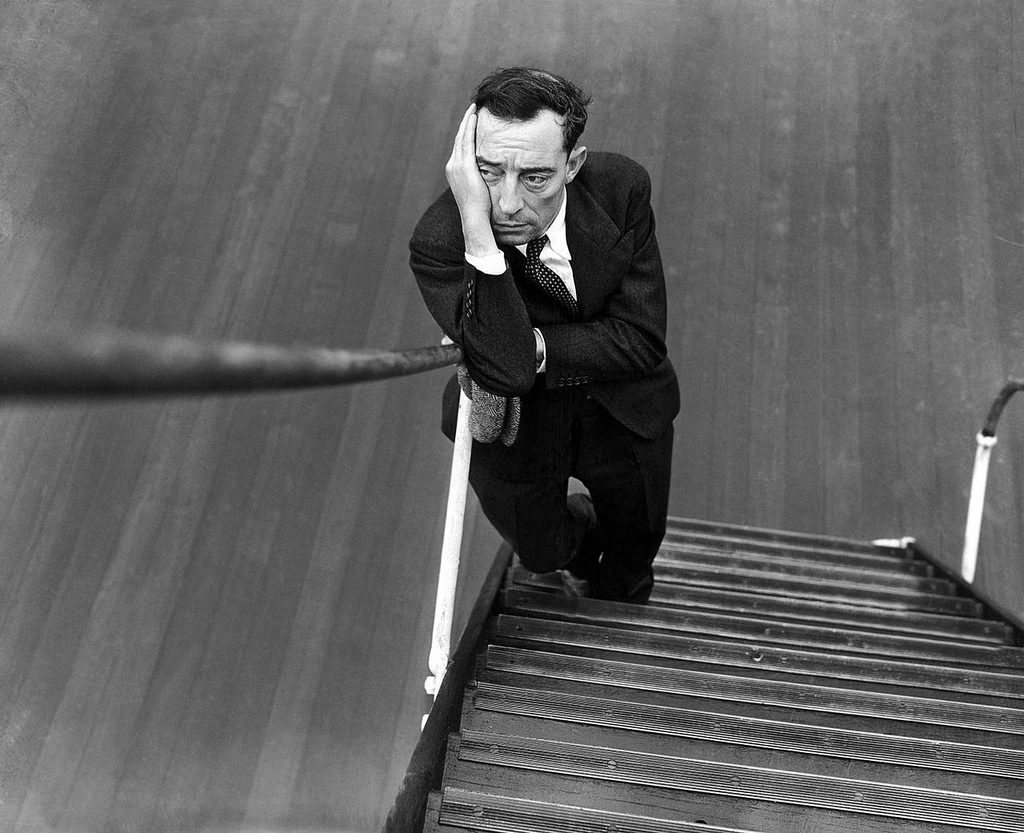 1934: If Buster Keaton was glad to be back in the United States, he certainly kept it a secret. The cameraman asked the film comedian to smile and this is the result. He was aboard the Ile de France on his return from a 5 months tour of the continent.