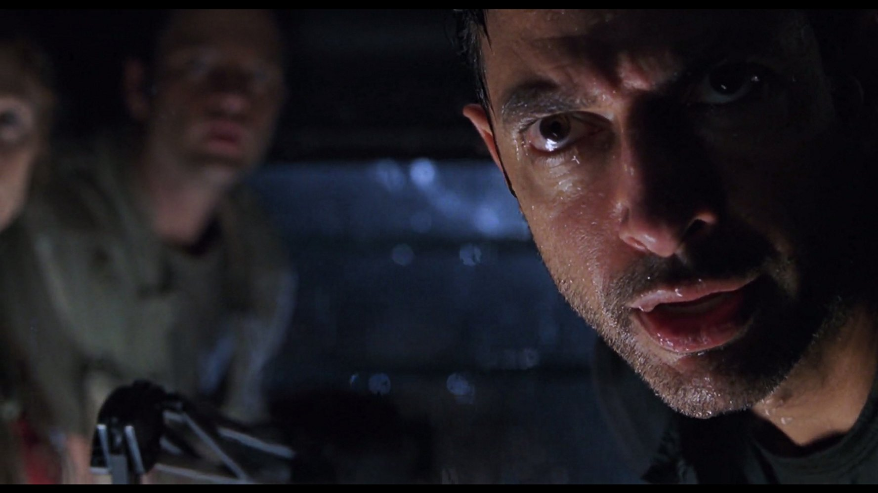 A rain-soaked Jeff Goldblum stares down a T-Rex in THE LOST WORLD: JURASSIC PARK (1997)
