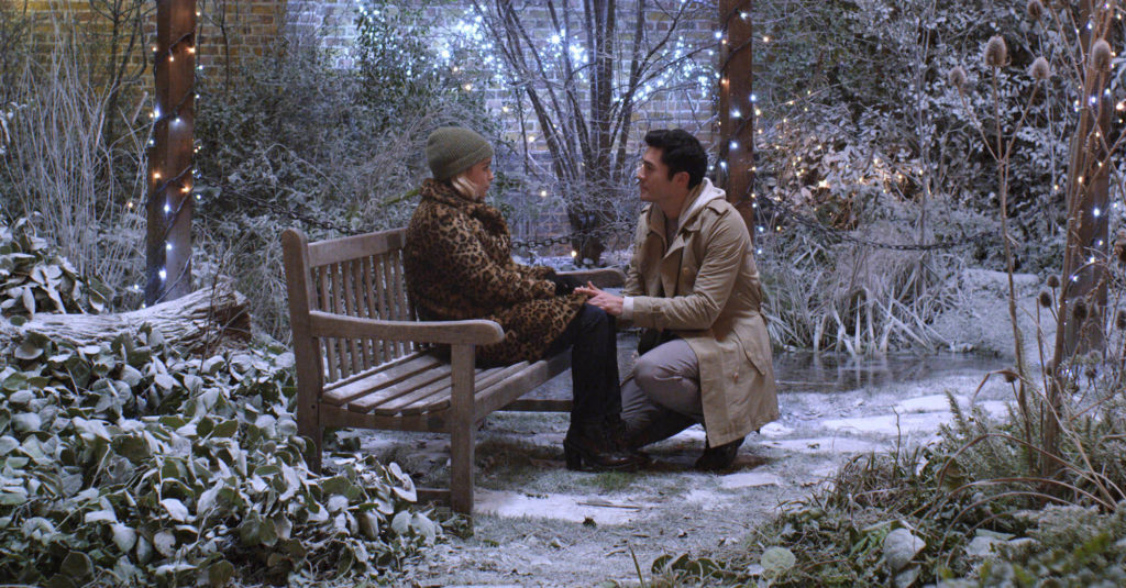 Emilia Clarke and Henry Golding talk on a bench in a snowy garden in LAST CHRISTMAS (2019)