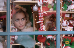 Emilia Clarke looks through a window of the Christmas shop in LAST CHRISTMAS (2019).