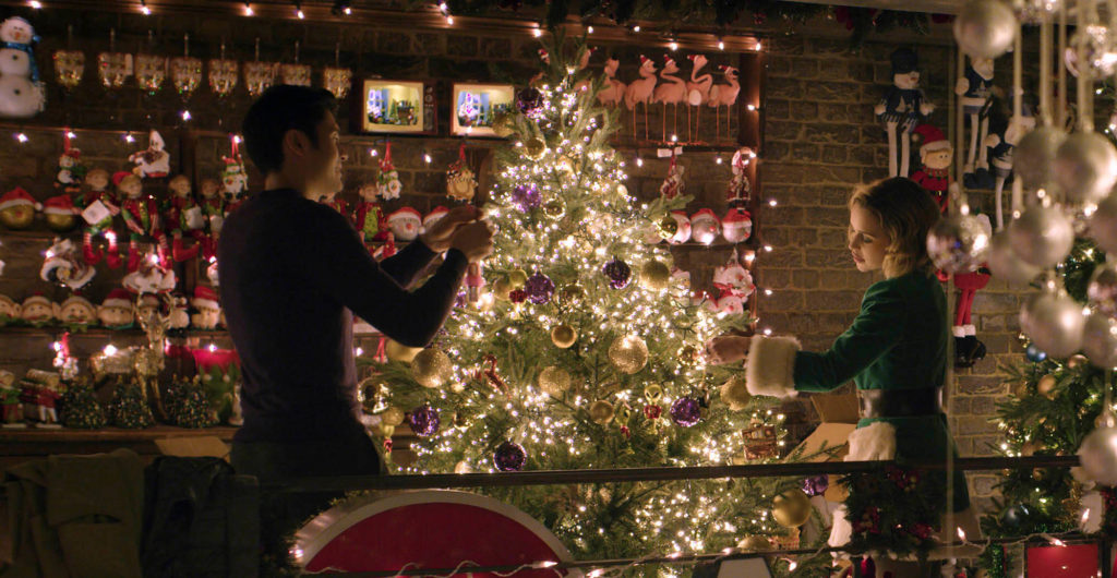 Emilia Clarke and Henry Golding trim a tree in LAST CHRISTMAS (2019)