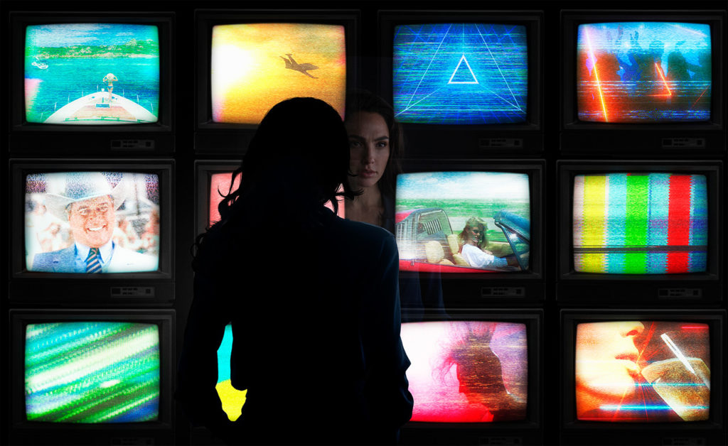 Gal Gadot in front of a screen of TVs in WONDER WOMAN 1984