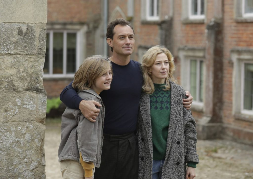 Charlie Shotwell, Jude Law, and Carrie Coon pose outside of their new home for a photograph in THE NEST (2020)